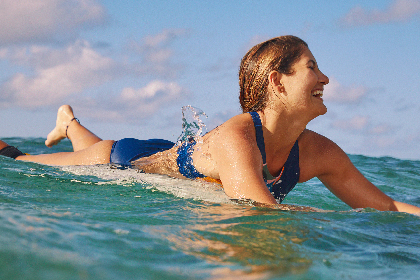 woman laughing in the ocean on surfboard