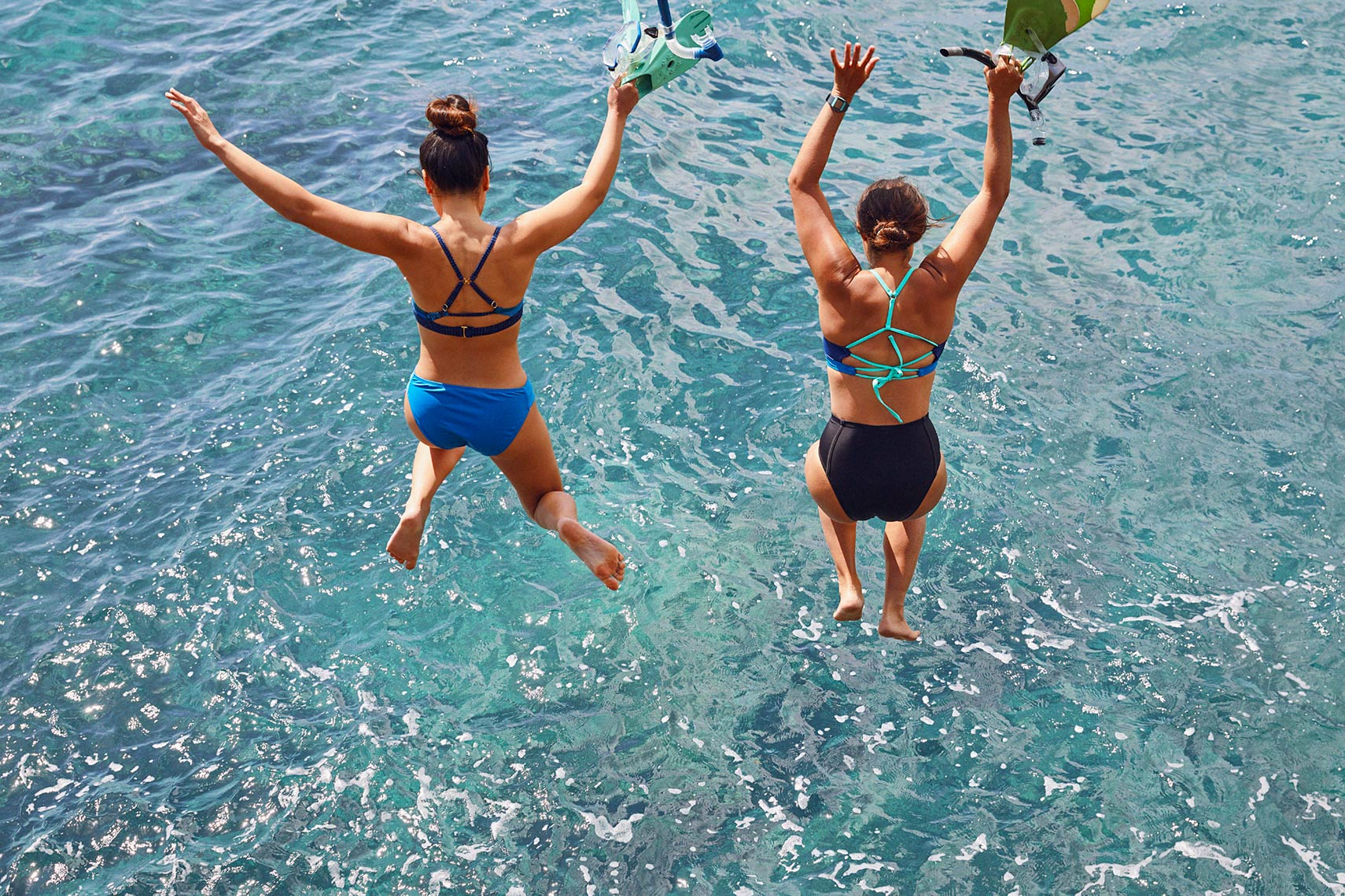 two women jumping into ocean in swimwear with hands overhead