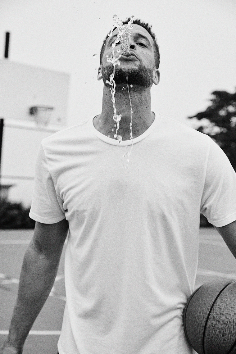 Man playfully spitting water at camera with basketball