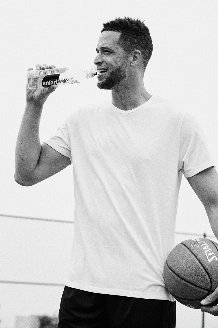 Man drinking Smartwater after playing basketball black and white