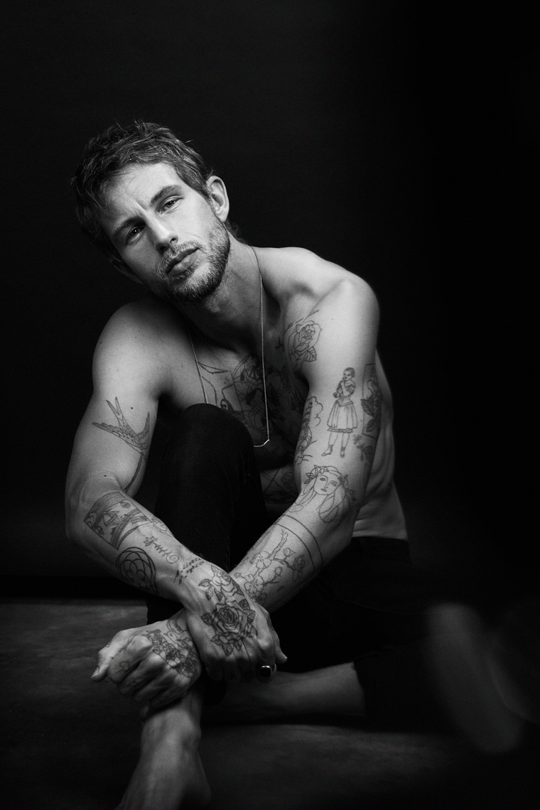 Black and white portrait of shirtless man with tattoos