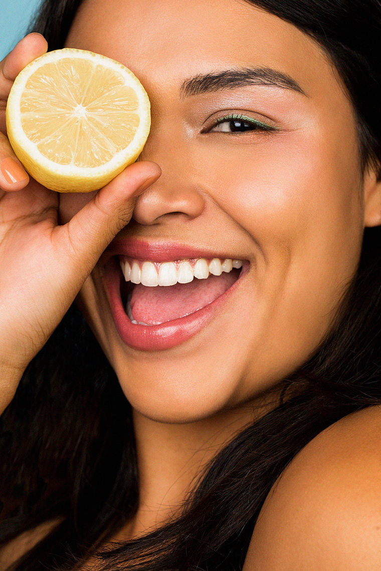 Beauty portrait of smiling woman holding lemon