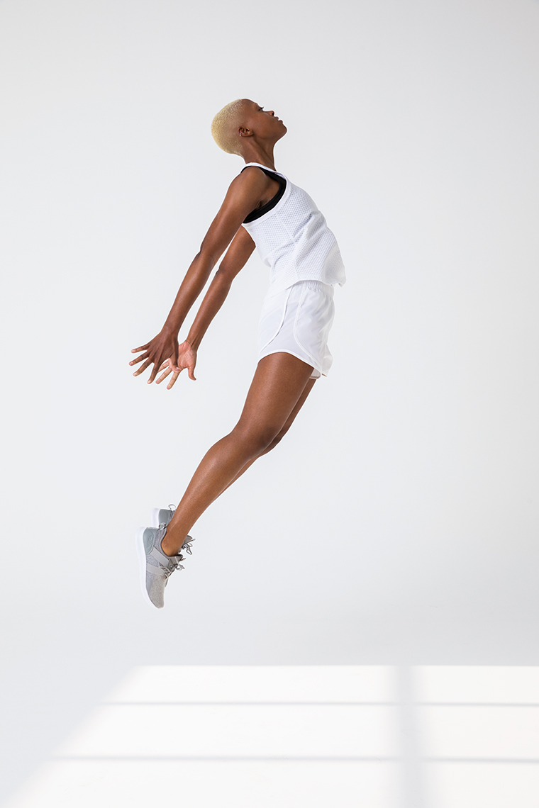 Portrait of non-binary African American mode jumpingl in white activewear in white studio