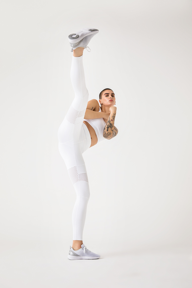 Athlete in white activewear kicking in white studio studio