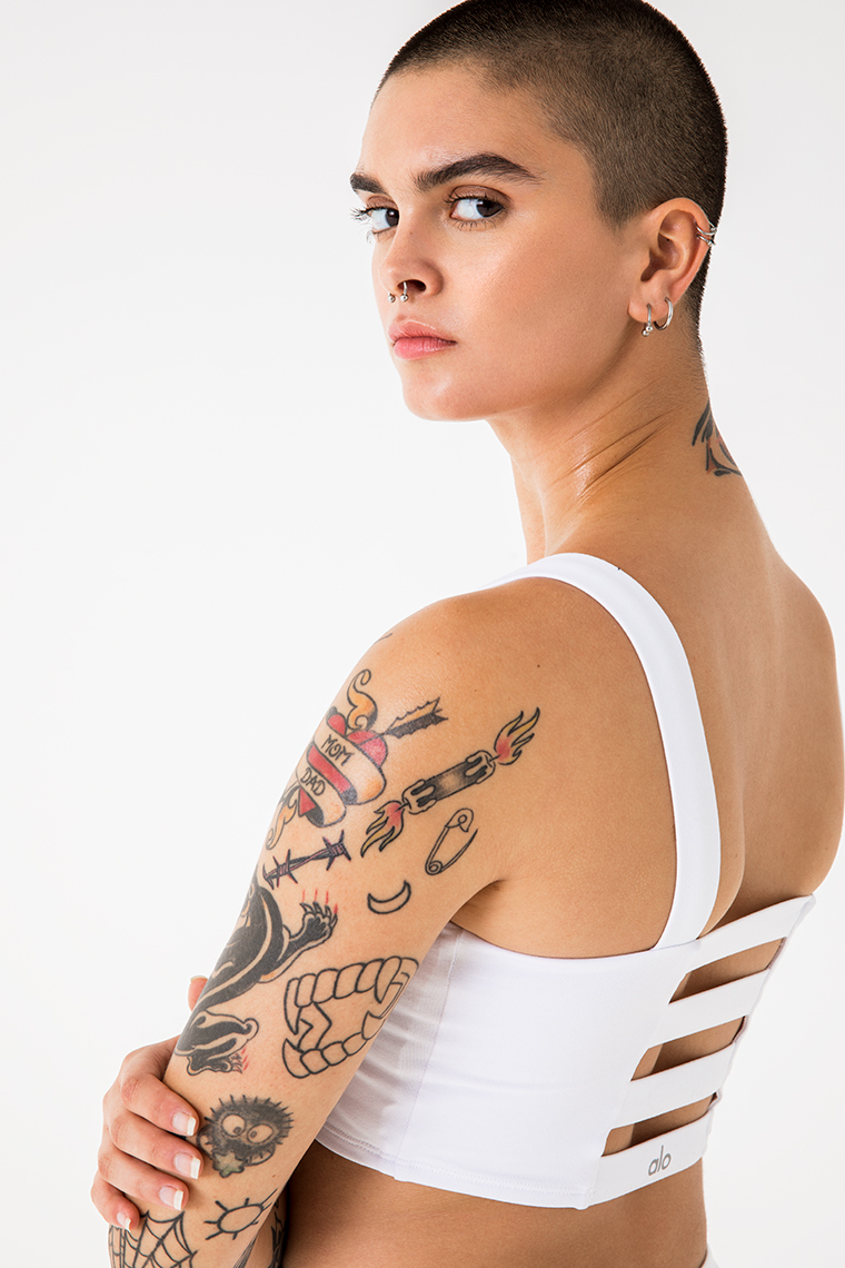 Portrait of woman with shaved head and tattoos  in sports bra