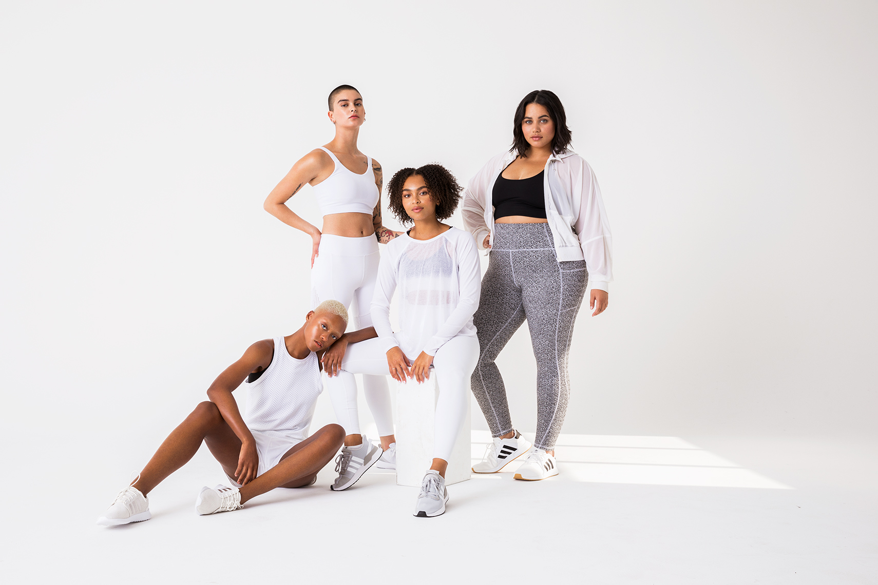 Portrait of a group of diverse models white in activewear on white background