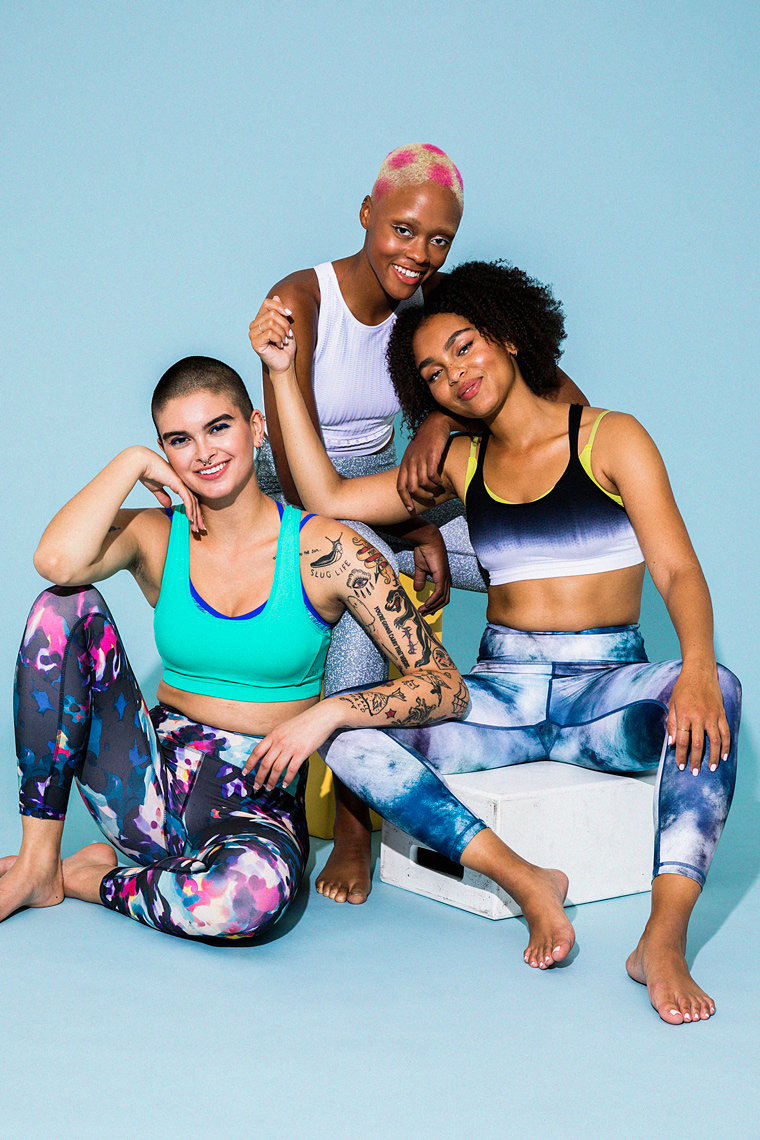 Group portrait of three women in colorful activewear laughing together
