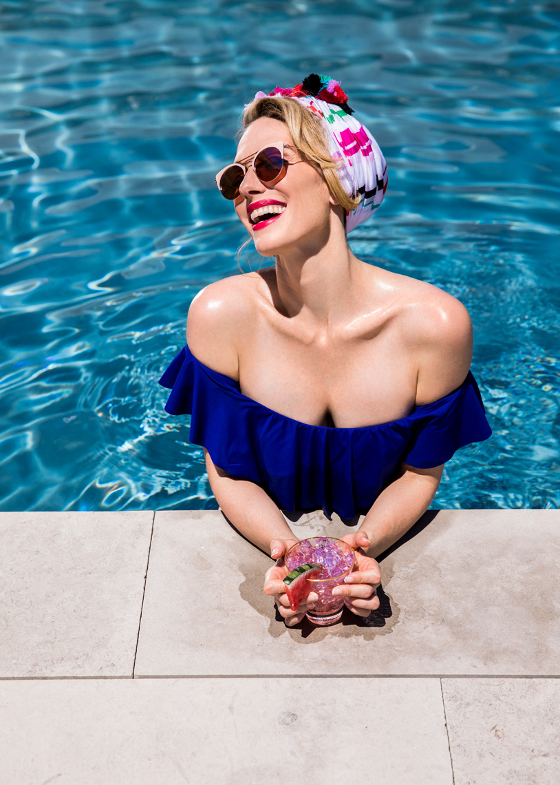 Fashionable woman in pool drinking cocktail