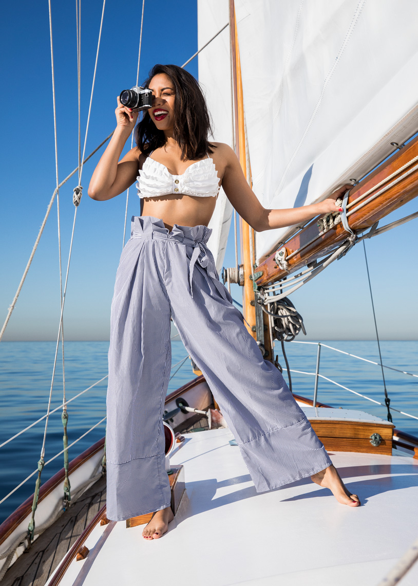 woman on sailboat taking pictures in cute outfit