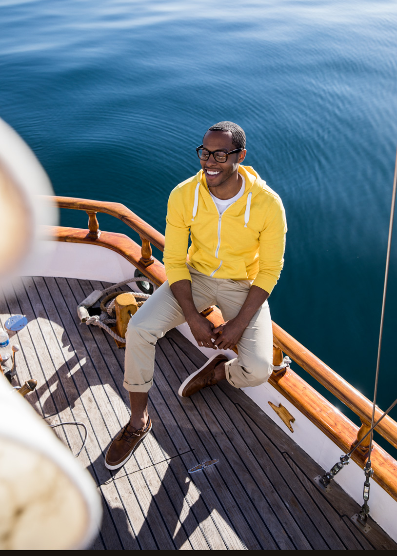 man sitting on sailboat in yellow sweatshirt
