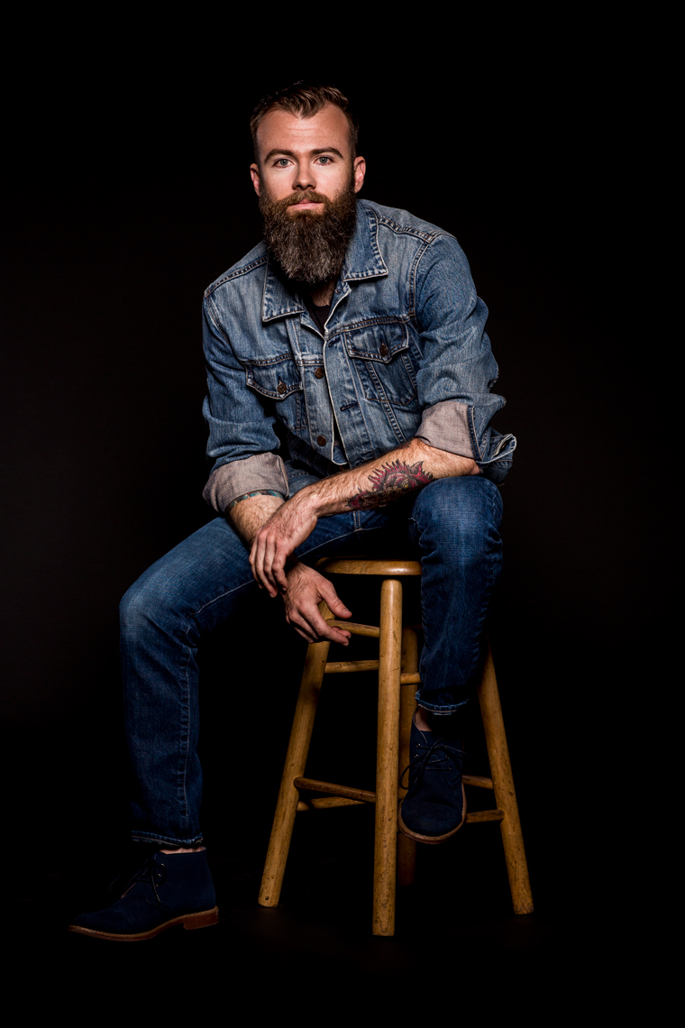 Bearded man in denim posing for studio portrait