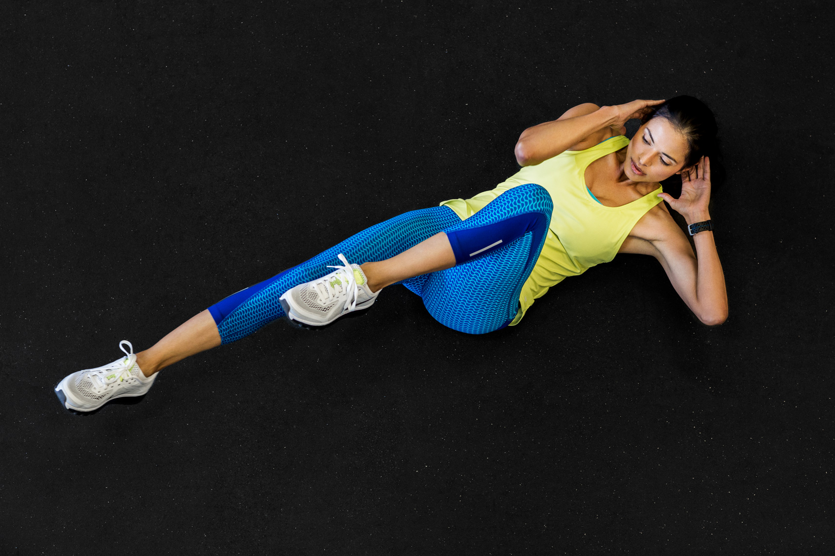 Woman doing bicycle crunches in colorful clothes shot from above