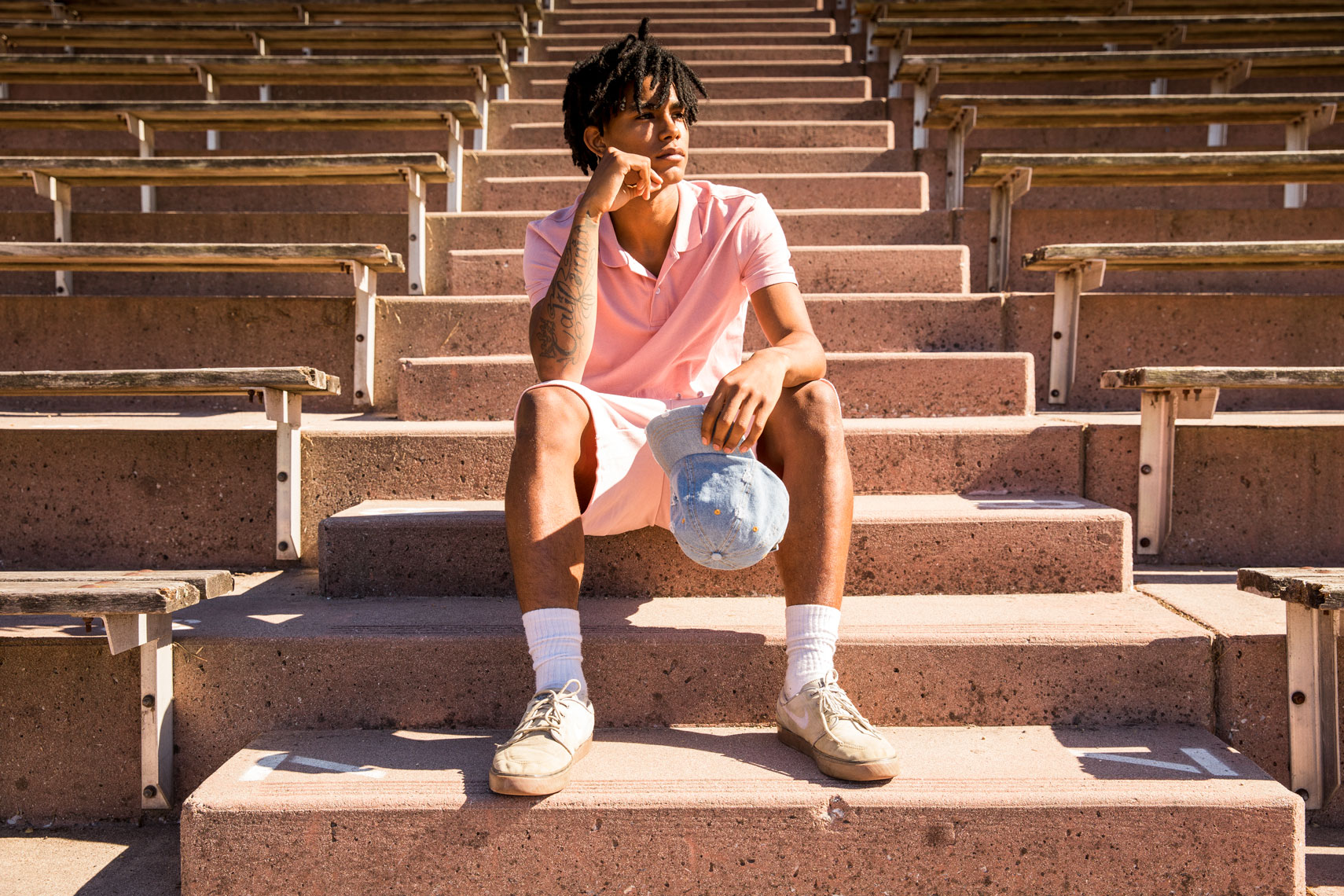 Portrait of man wearing pink sitting on stadium steps