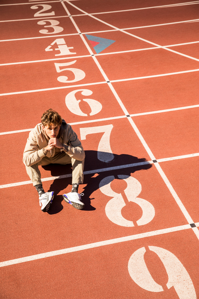 Man sitting on a running track