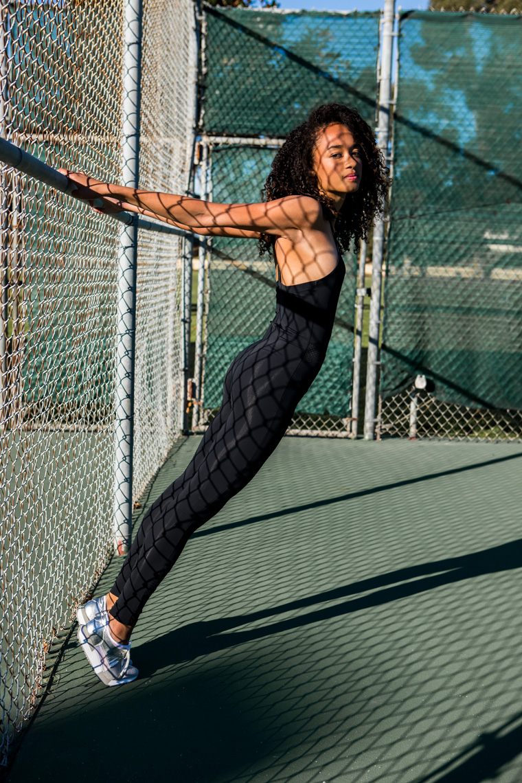 Woman in black catsuit on tennis court