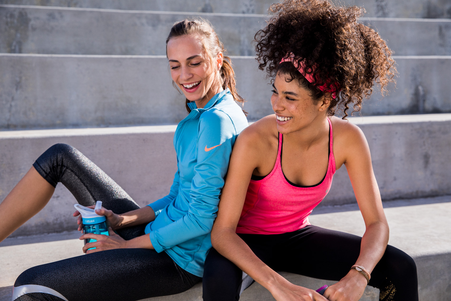 girls laughing after workout on cement bleachers