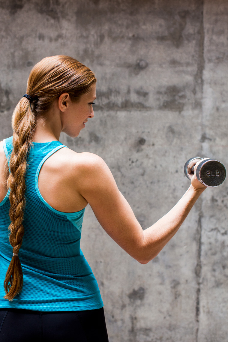 Woman doing bicep curls with cement wall backdrop
