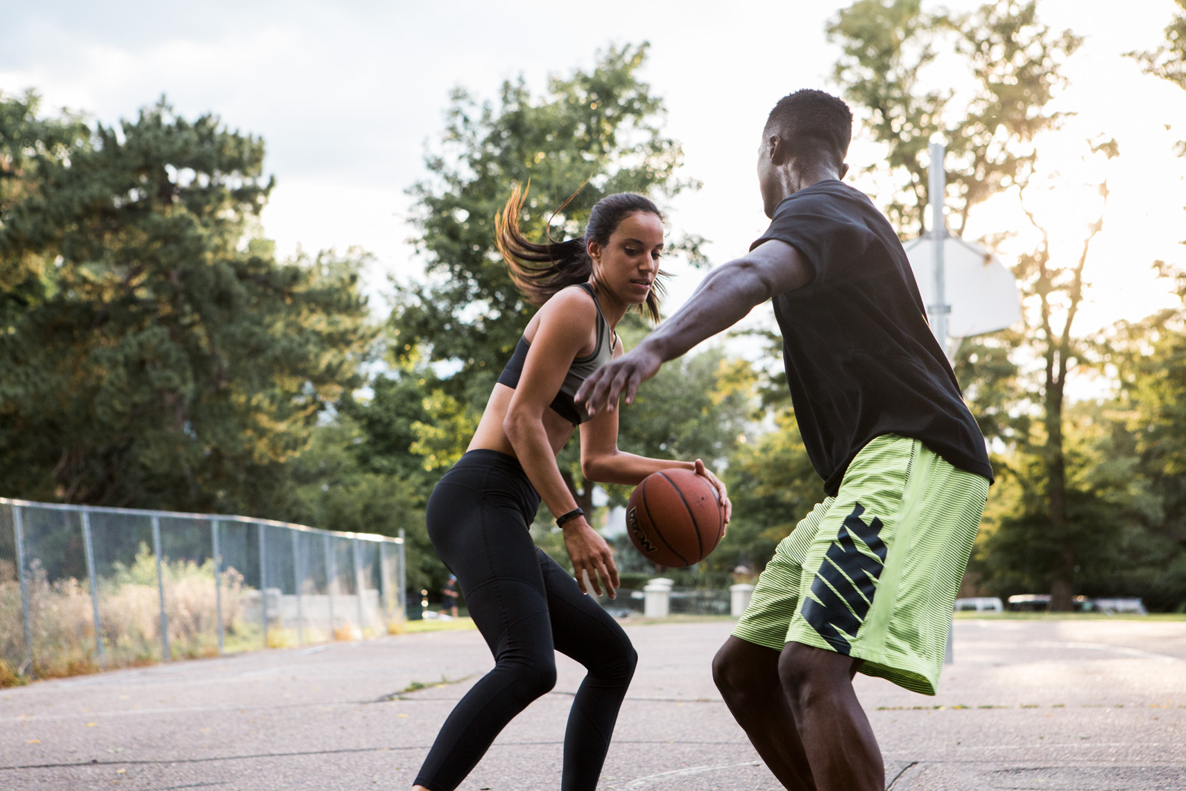 Man and woman playing basketball outdoors