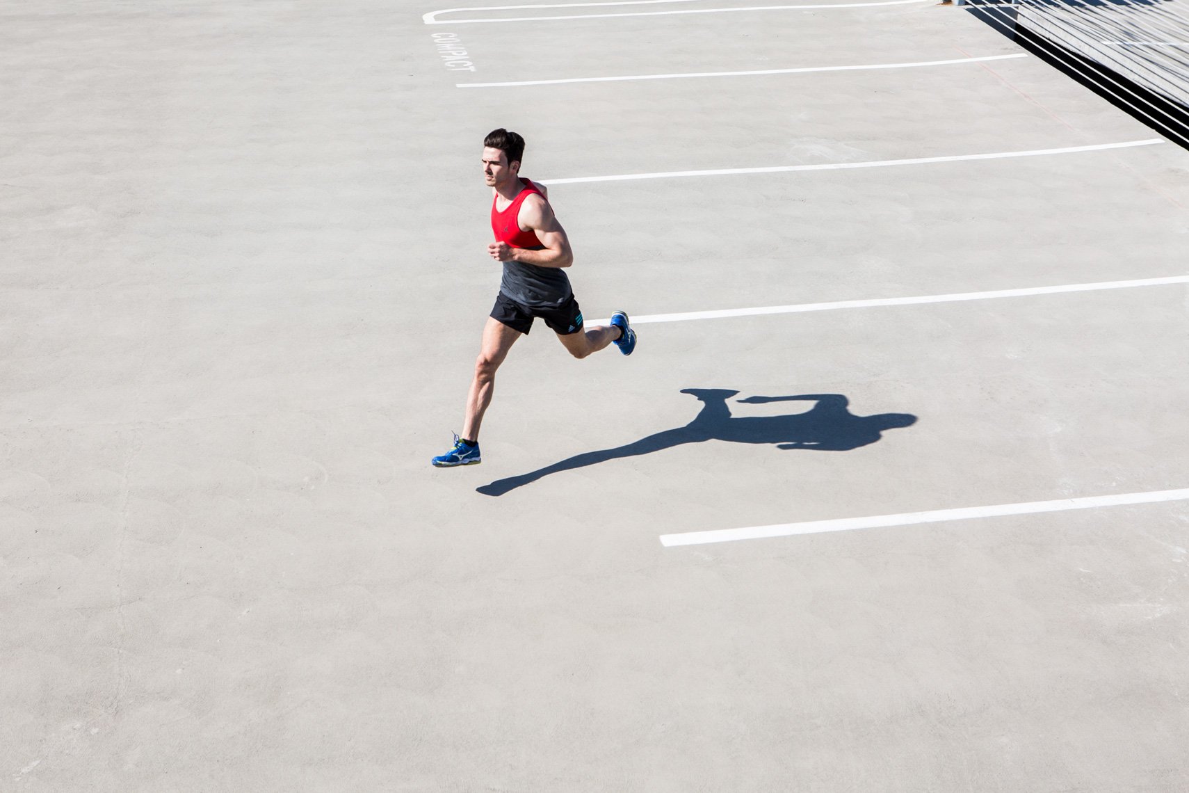 Man running through parking lot with shadow