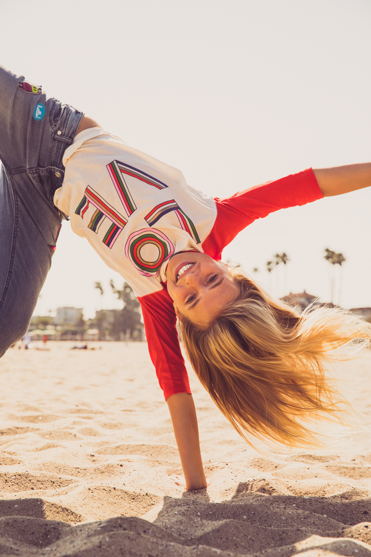 Young girl doing cartwheels on the beach in Love shirt