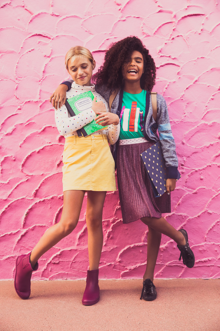 Young girl friends in back to school clothes laughing on pink wall