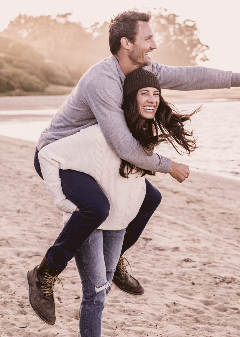 Couple laughing on beach while giving a piggy back ride
