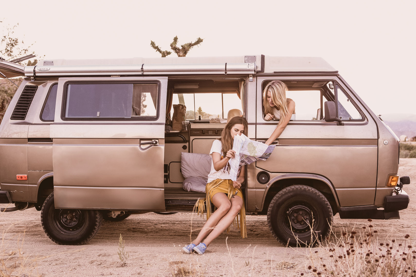 girls sitting in volkswagon van reading a map on road trip