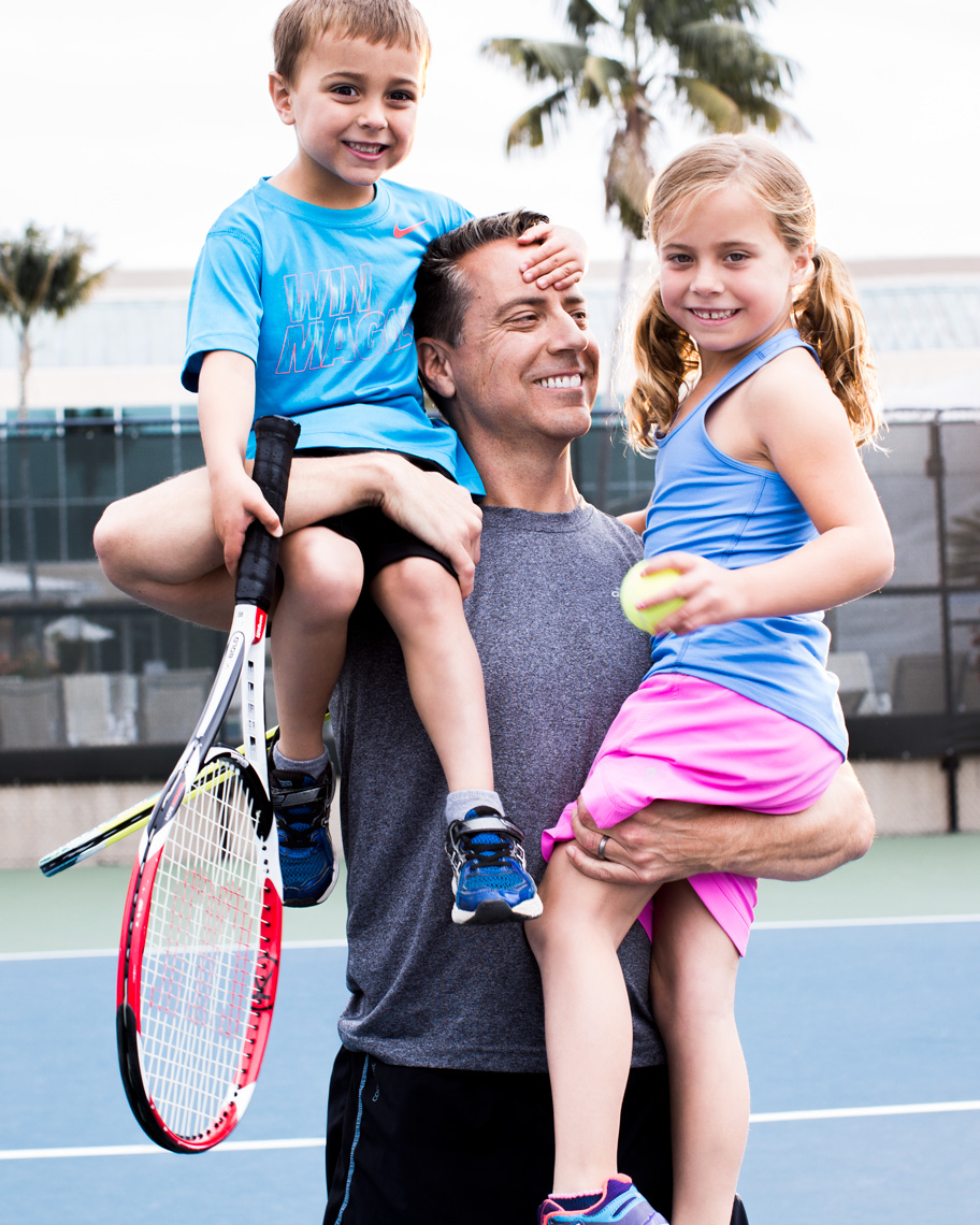 Dad and two children playing tennis