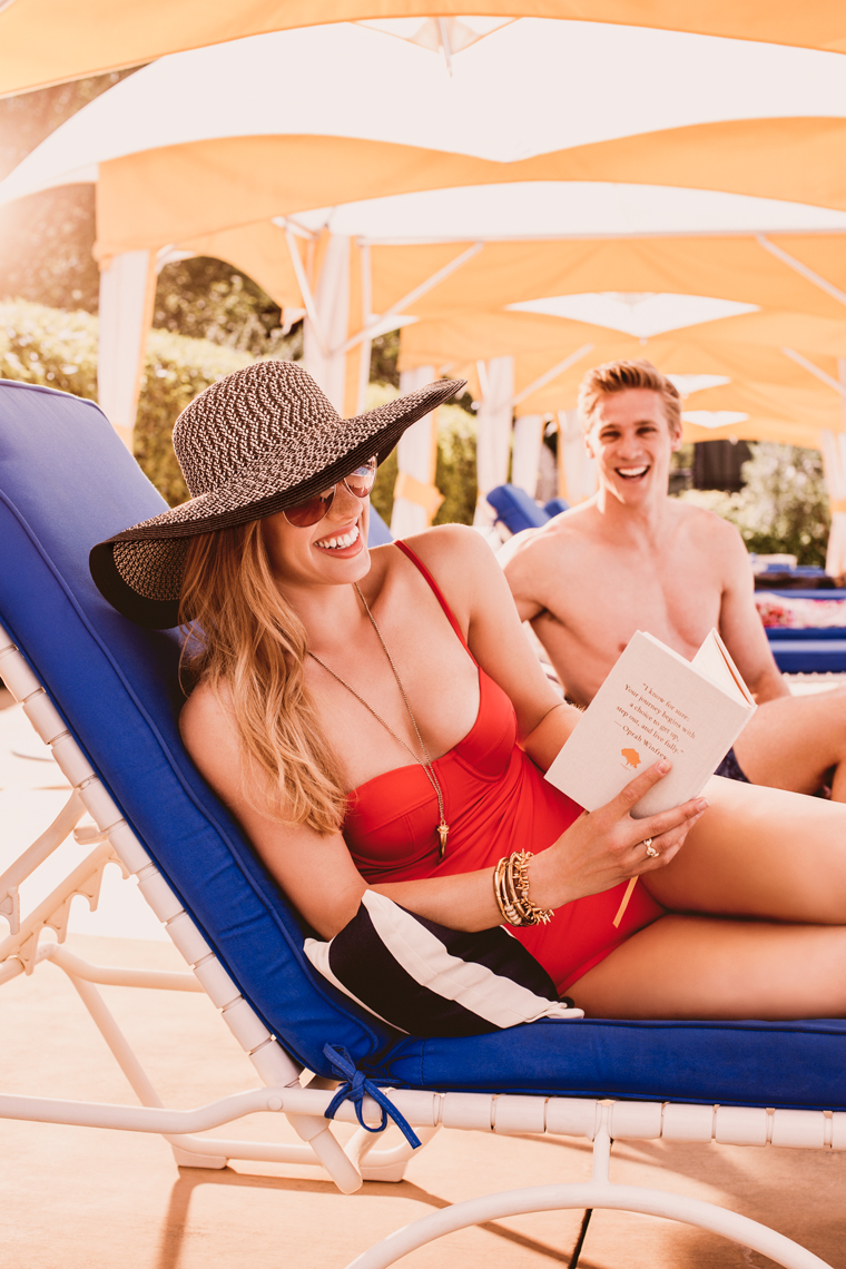 Couple laughing by the pool in red bathing suit