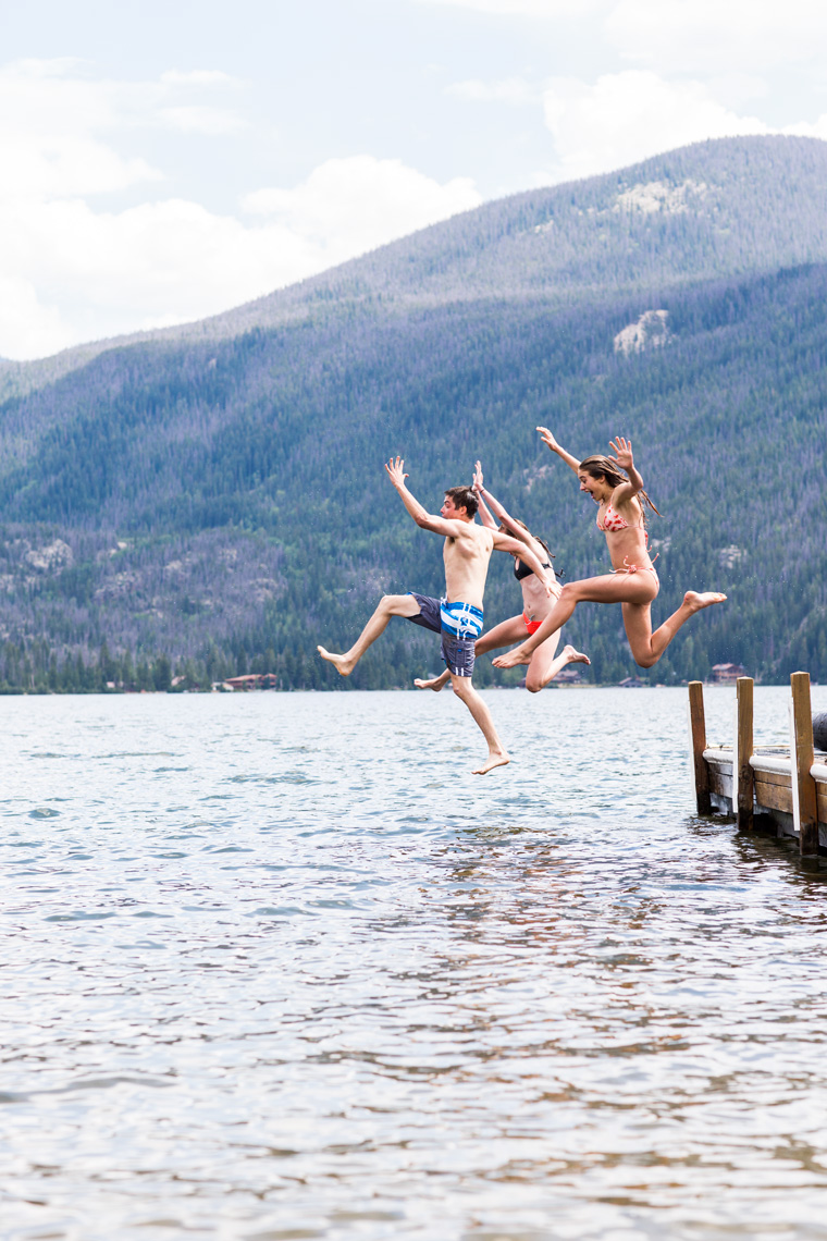 Friends jumping off a dock into a lake