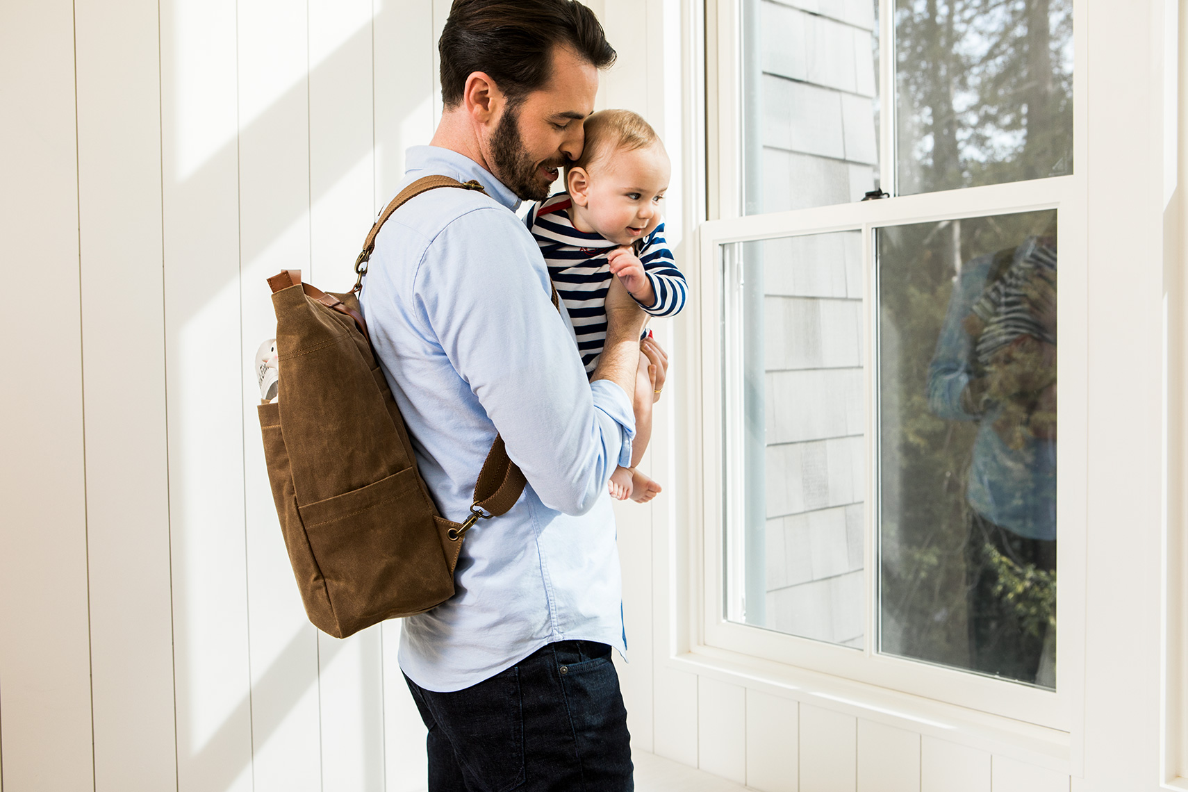 Father holding baby while looking out the window