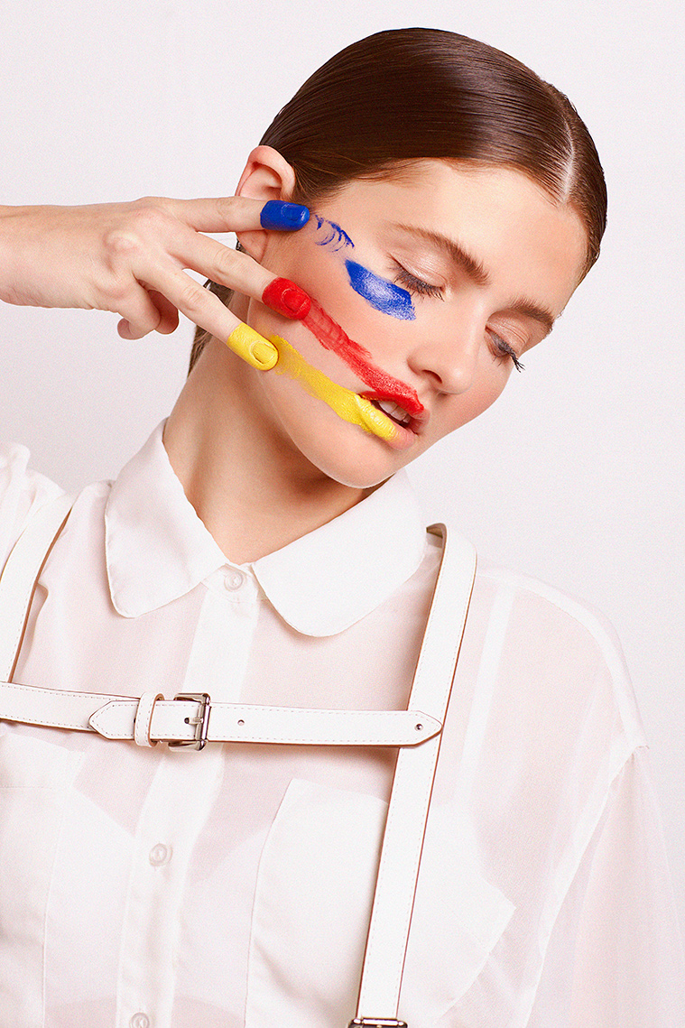 Portrait of woman wearing white and painting face with primary colors