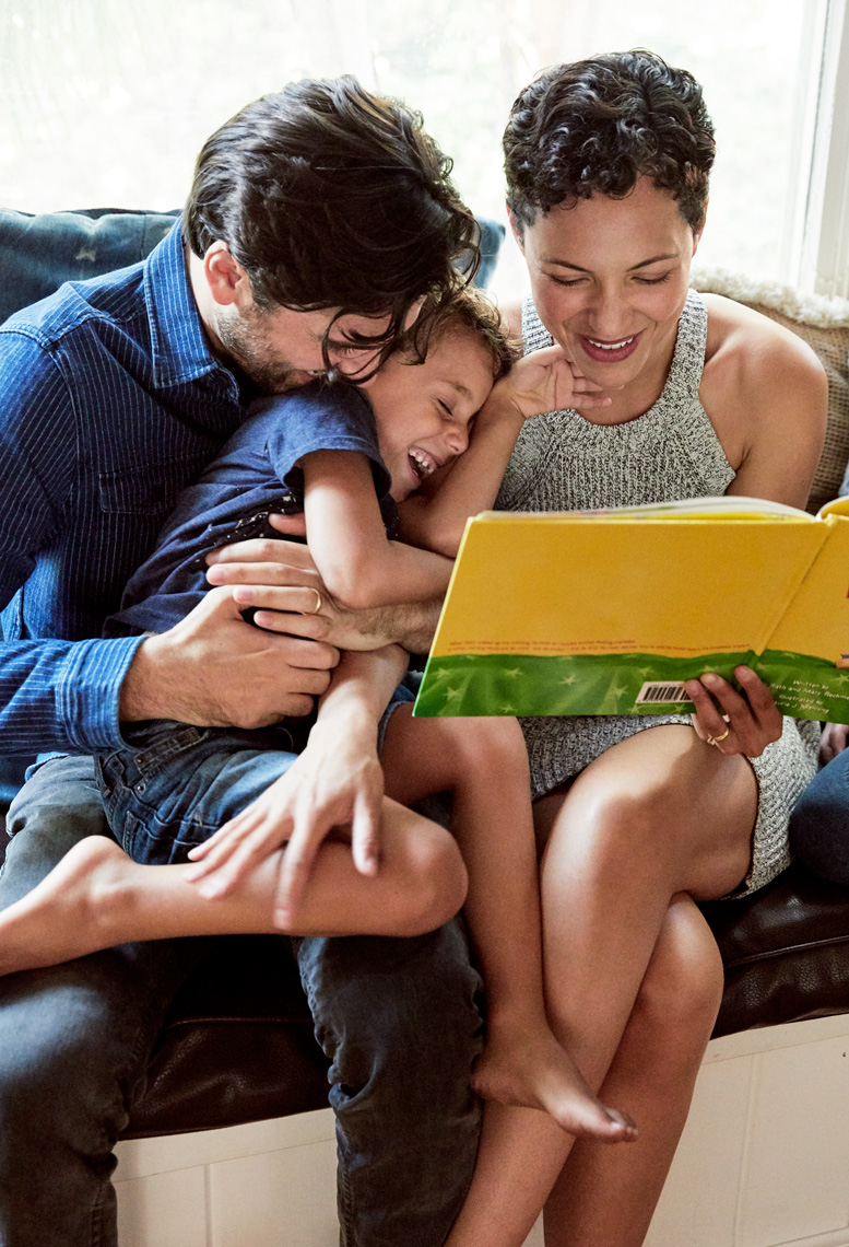Mom and dad reading a book to their son while playing