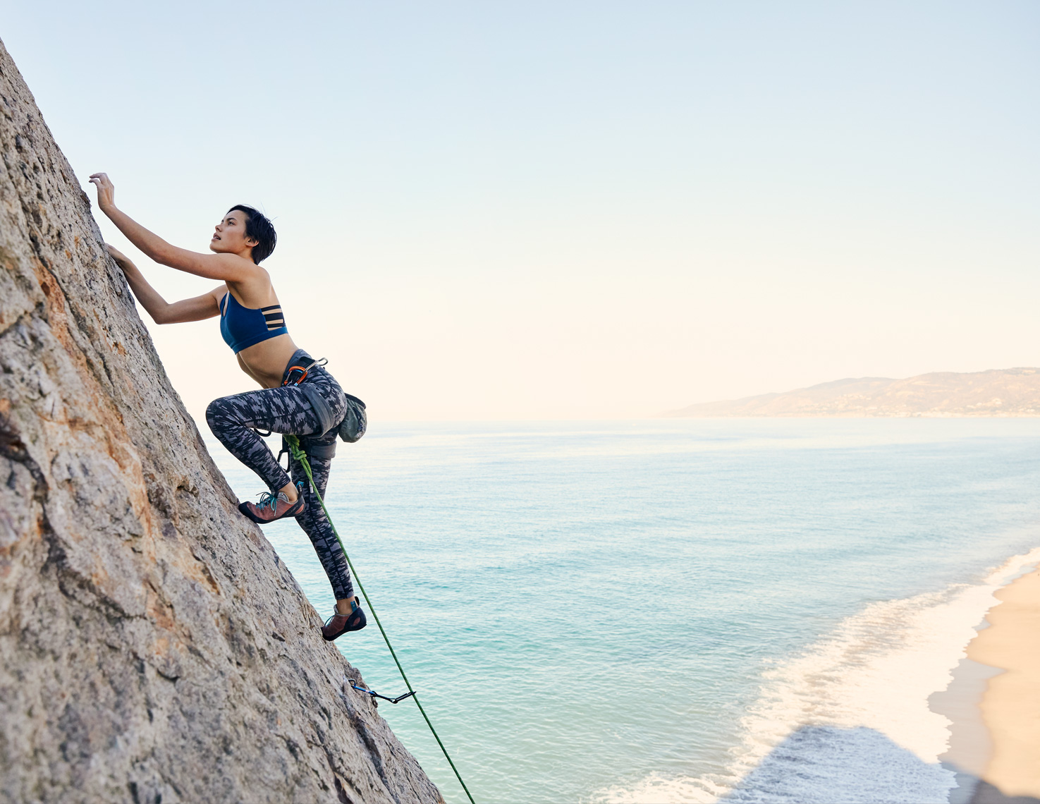Woman rock climbing with the ocean behind her