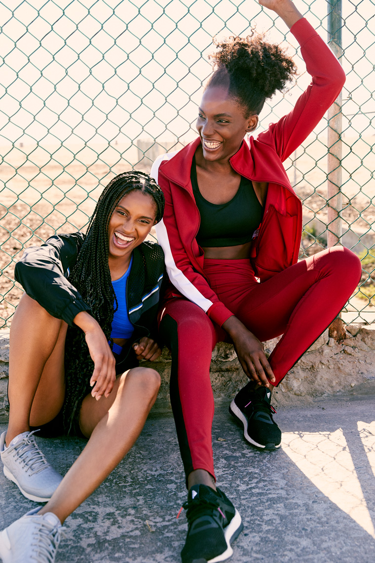 two women in athletic wear sitting against a fence and laughing