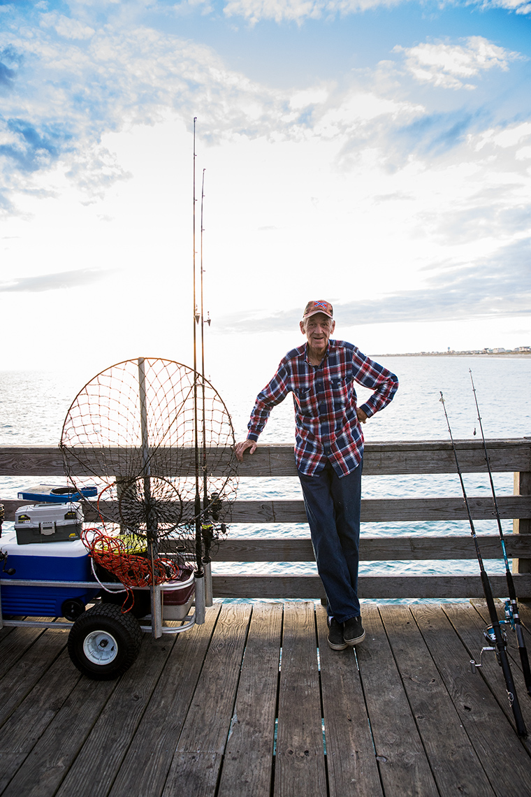 Portrait of man on a pier near fishing equipment